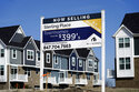 An advertising sign for building land stands in front of a new home construction site in Northbrook, Ill., Sunday, March 21, 2021.  The red-hot U.S. housing market is widening the gap between what a home is objectively worth and what eager buyers are willing to pay for it. Fierce competition amid an ultra-low inventory of homes on the market is fueling bidding wars, prompting a growing share of would-be buyers to sweeten offers well above what sellers are asking.   (AP Photo/Nam Y. Huh)