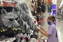 A young customer looks at a Halloween mask at a Party City store, Wednesday, Oct. 6, 2021, in Miami.  Americans continued to spend at a solid clip in September despite rising prices and snarled global supply chains that are limiting the flow of goods. Retail sales rose a seasonally adjusted 0.7%  in September  from the month before, the U.S. Commerce Department said Friday, Oct. 15.  (AP Photo/Marta Lavandier)