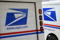 FILE - In this Aug. 18, 2020, file photo, mail delivery vehicles are parked outside a post office in Boys Town, Neb.  Oshkosh Defense says, Tuesday, June 22, 2021,  it will make new delivery vehicles for the U.S. Postal Service in Spartanburg, S.C., creating 1,000 new jobs. The Wisconsin company says it will reconfigure a warehouse with features needed to do large-scale manufacturing.  (AP Photo/Nati Harnik, File)