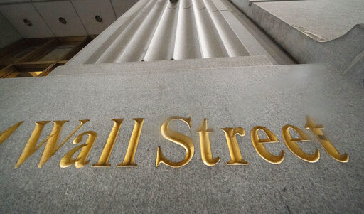 FILE - In this Nov. 5, 2020 file photo, a sign for Wall Street is carved in the side of a building, in New York. Technology stocks were off to a good start on Wall Street, but other parts of the markets weren't as strong, leaving major indexes mixed in the early going. The S&P 500 was up 0.3% in the first few minutes of trading Monday, Jan. 25, 2021, and the tech-heavy Nasdaq climbed 1.4%. (AP Photo/Mark Lennihan, File)
